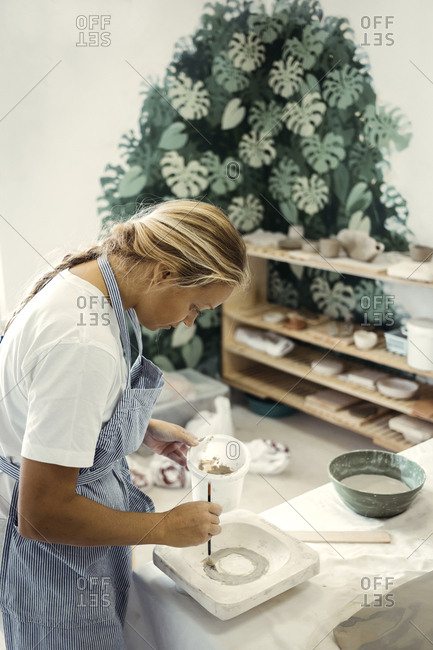 Female potter painting clay into a mold in a workshop