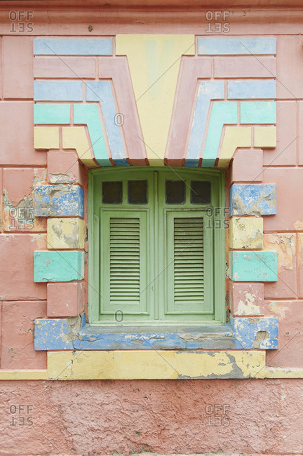 Colorful facade surrounding green shutters on window, Guamare, Rio Grande do Norte, Brazil