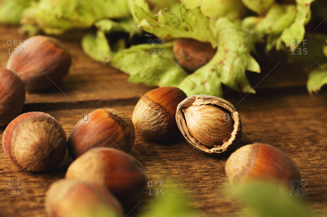 Close up of hazelnuts on wooden surface with one cracked open nut