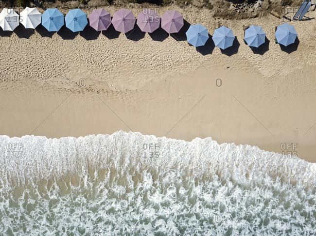 Aerial view of row of sun umbrellas, Balangan beach, Bali, Indonesia
