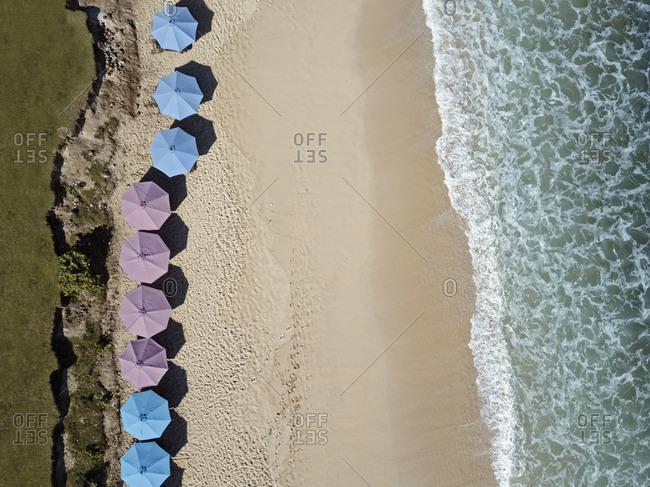 Bird's eye view of row of sun umbrellas, Balangan beach, Bali, Indonesia