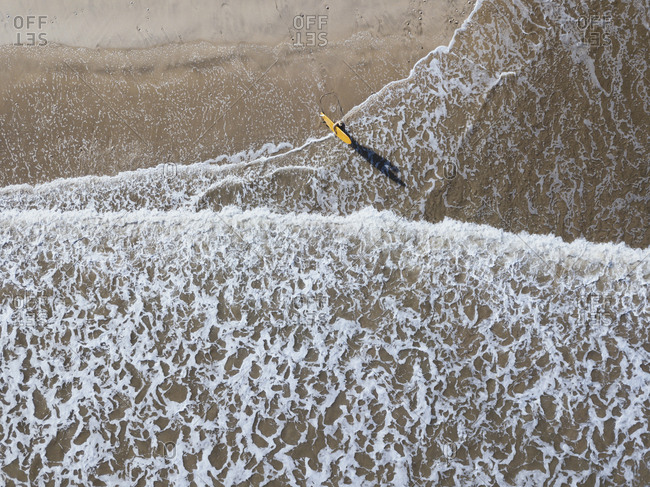 A surfer heading out to sea, Jimbaran beach, Bali, Indonesia from above