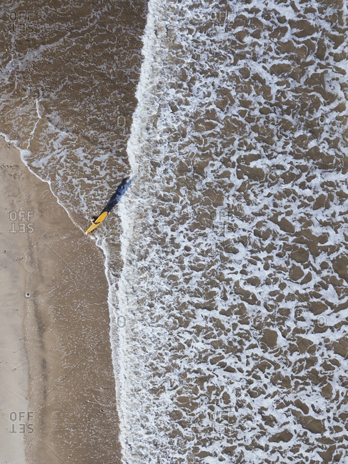 A surfer heading out toward waves, Jimbaran beach, Bali, Indonesia from above