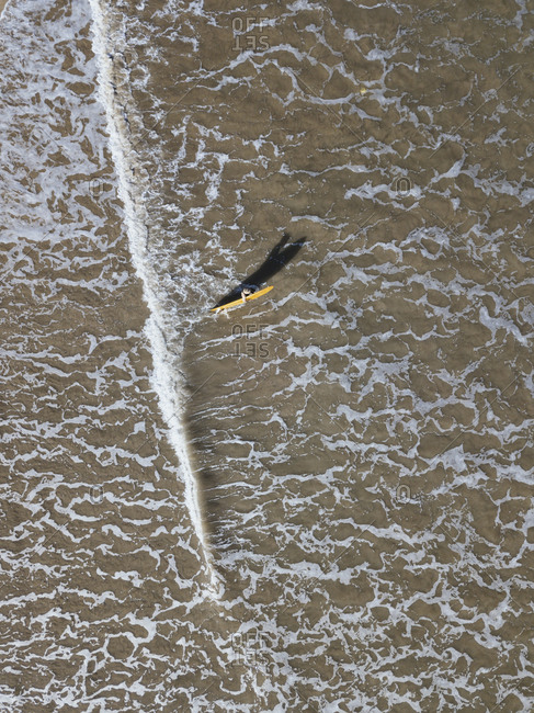 Aerial view of a surfer heading out toward waves, Jimbaran beach, Bali, Indonesia