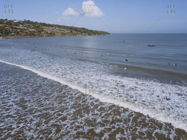 Several surfers in the ocean, Jimbaran beach, Bali, Indonesia