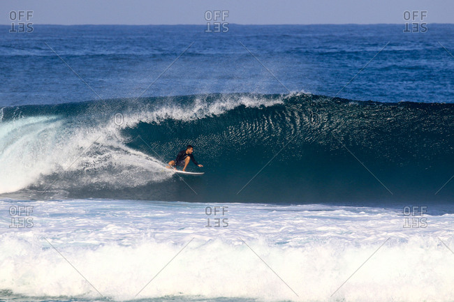 A surfer rides a wave in Indonesia