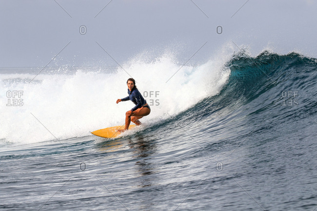 A young woman surfs a perfect wave