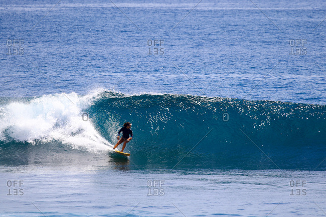 A young woman surfs in Indonesia