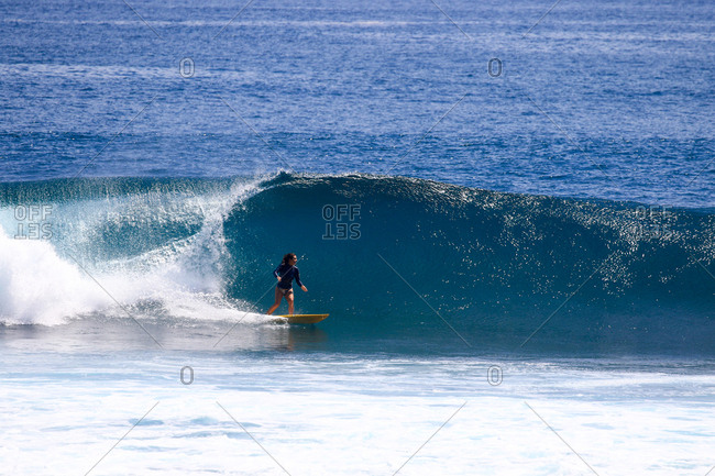 A young woman surfs on a sunny day