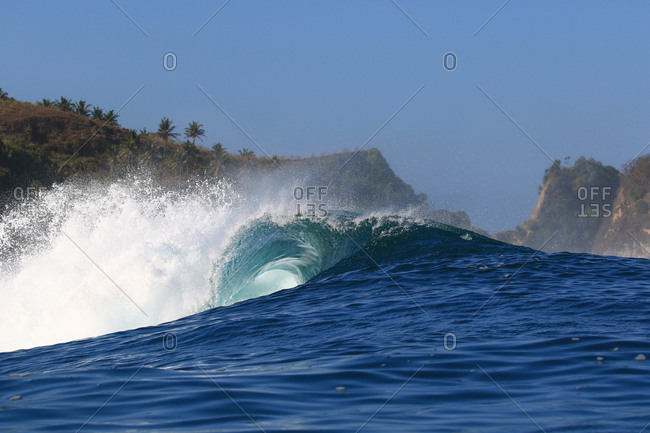 A perfect wave barrels over a tropical reef