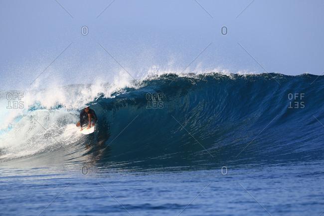 A surfer under a wave