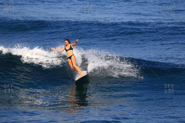 A female surfer has fun riding a longboard in Indonesia