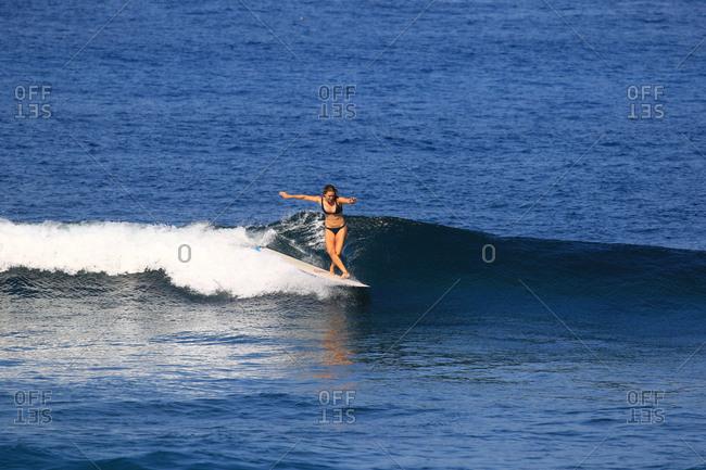 A female surfer rides a longboard in Indonesia
