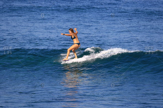 Woman surfs on a longboard in Indonesia
