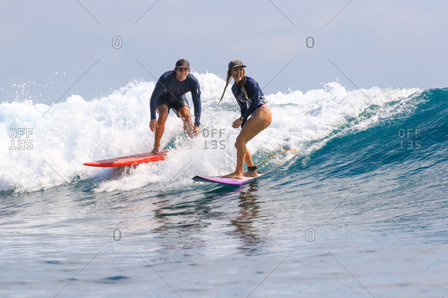 Husband and wife surf together on a wave