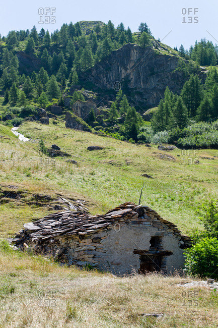 Shepherd's alpine chalet abandoned at altitude in a green alpine landscape in Northern Europe