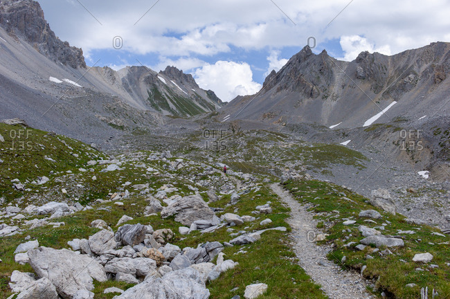 Woman hiking in distance in mountain landscape during a beautiful summer in Northern Europe