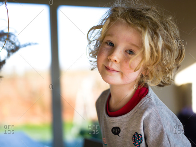 Smiling little girl indoors in the winter light with a mischievous look