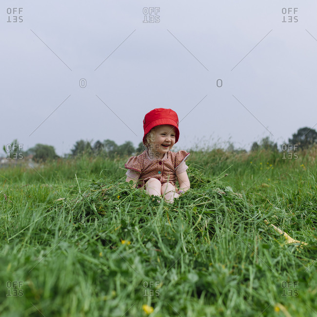 Little girl with a red hat sits on a small mound of fresh green hay in a meadow