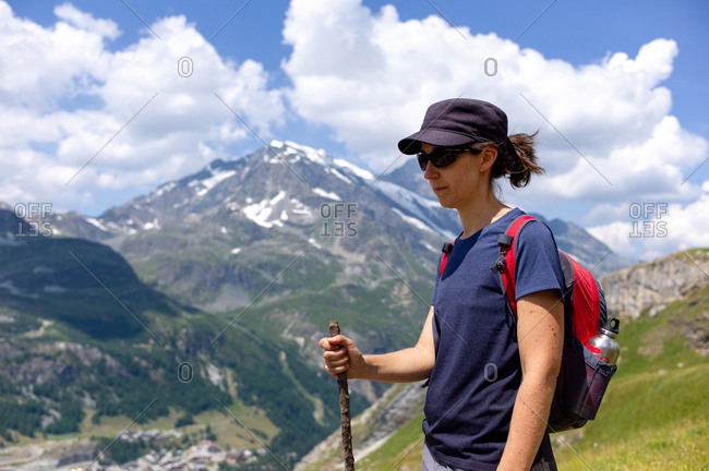 Woman with a backpack takes a break and contemplates the landscape during a hike