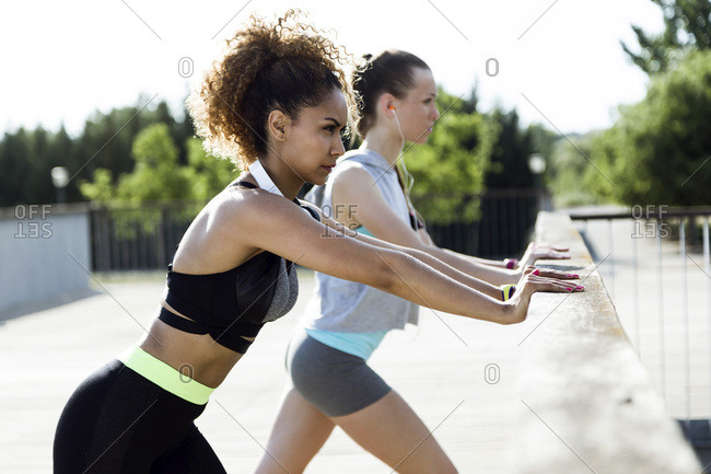 Two sporty young women stretching on bridge railing