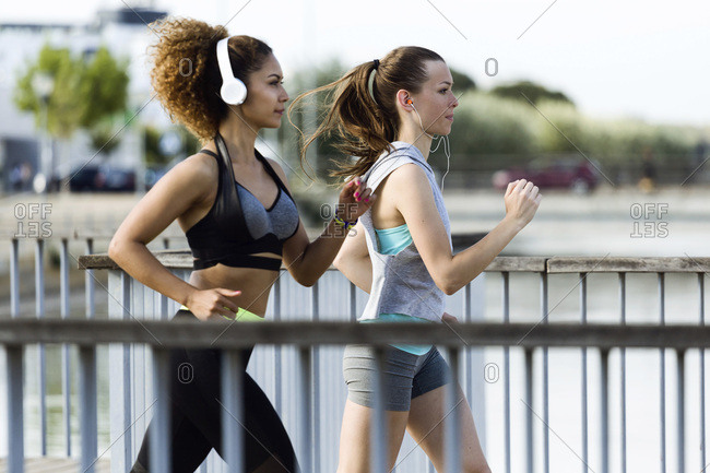 Two sporty young women running on a bridge