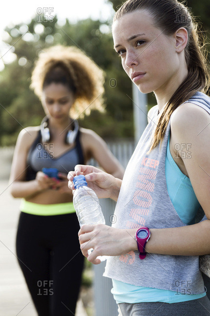 Two sporty young women finishing their workout