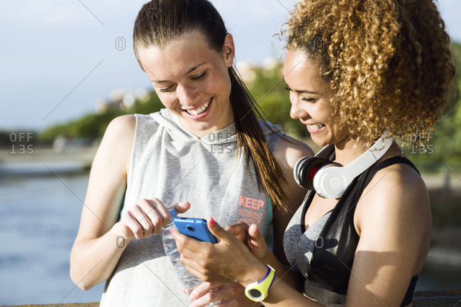 Two happy sporty young women checking cell phone