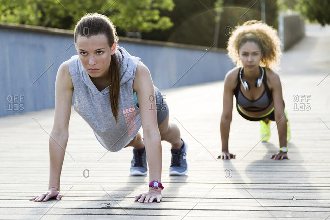 Two sporty young women doing push-ups on a bridge