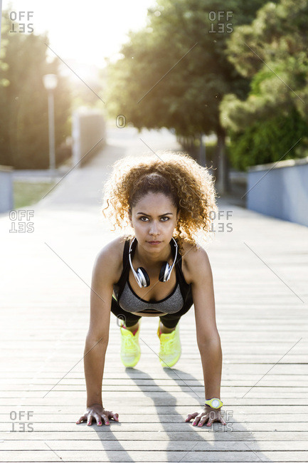 Sporty woman doing push-ups on a bridge