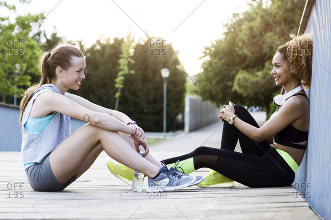 Two sporty young women relaxing on a bridge after workout