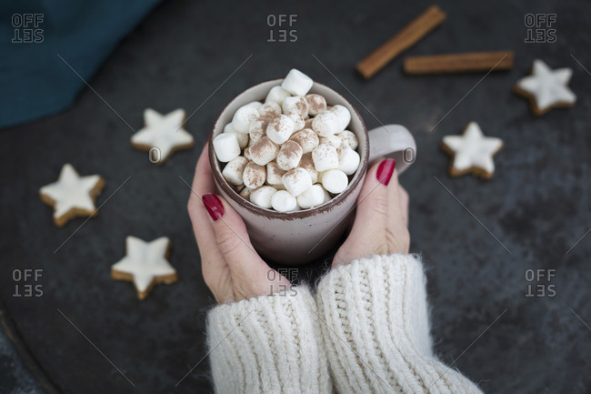 Woman's hands holding cup of Hot Chocolate with marshmallows at Christmas time