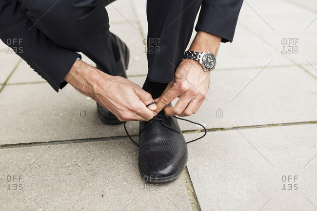 Businessman tying his shoe on pavement- close-up