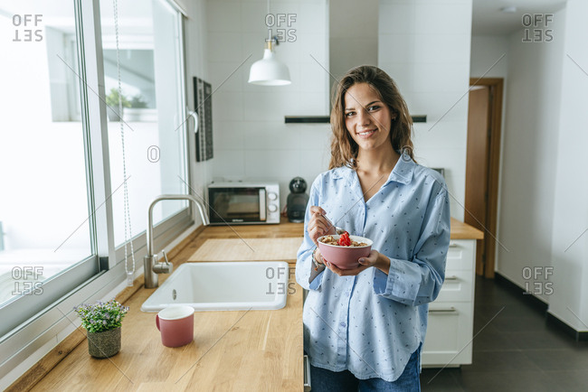 Portrait of young woman wearing pajama eating muesli in kitchen at home