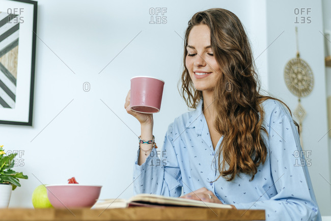 Smiling young woman reading book during breakfast at home