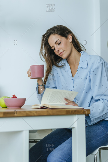 Young woman reading book during breakfast at home