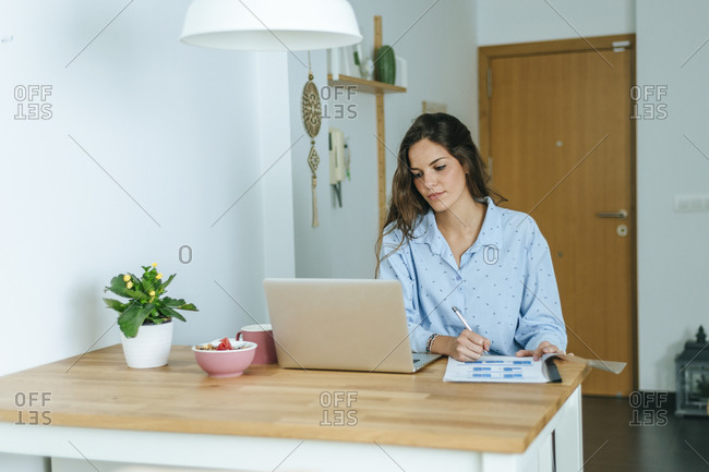 Young woman using laptop during breakfast at home