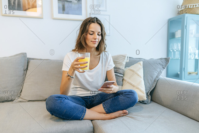 Young woman sitting on sofa with juice using cell phone