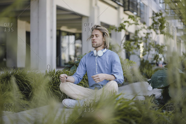 Young man meditating outside office building