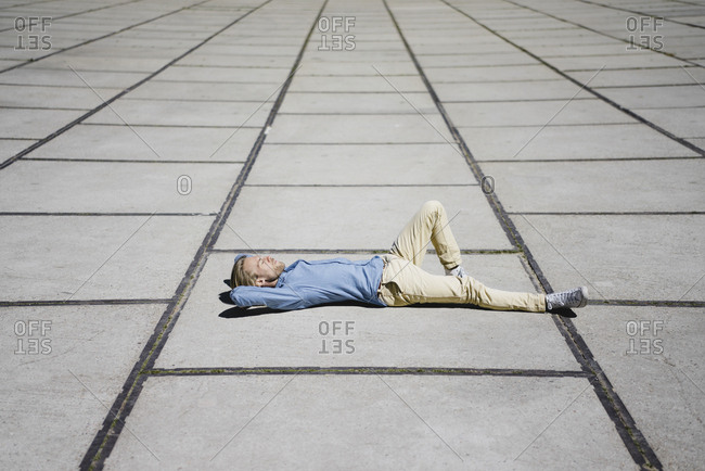 Young man lying on a square
