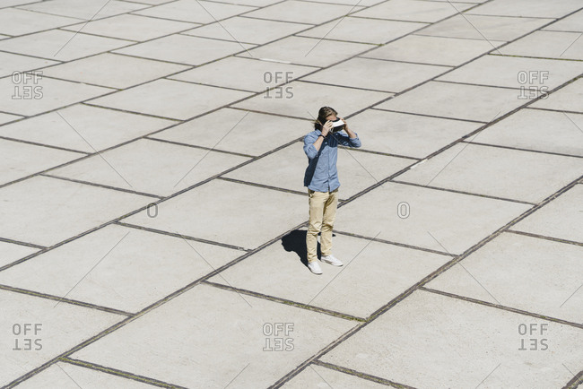 Young man with VR glasses standing on a square