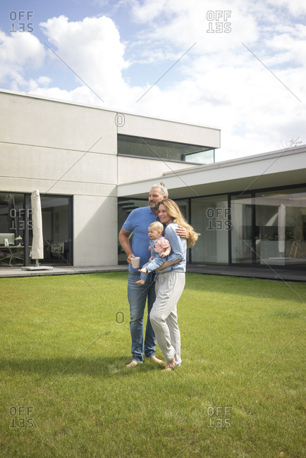 Family of three standing in garden of their home