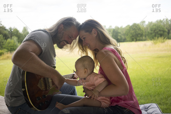 Father- mother and baby girl sitting outdoors with guitar