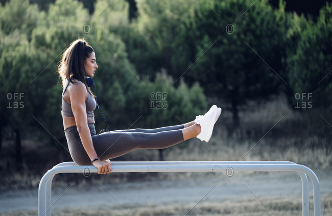 Young woman exercising on parallel bars