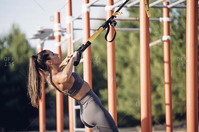 Young woman doing workout on calisthenics bars