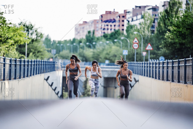 Three sporty young women running on a street