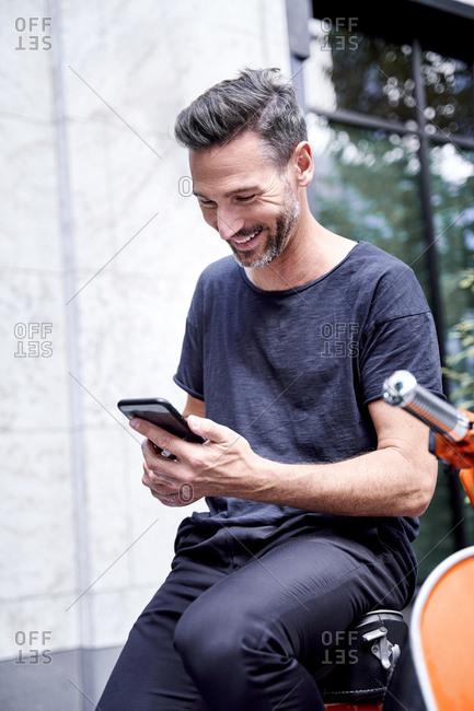 Mature man using smartphone- sitting on motor scooter