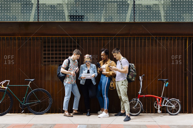 Students standing in the street- holding smartphones- reading papers