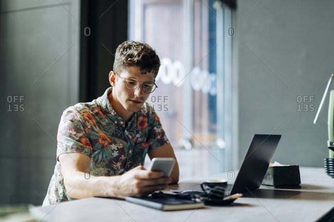 Young man sitting in cafe- using smartphone and laptop