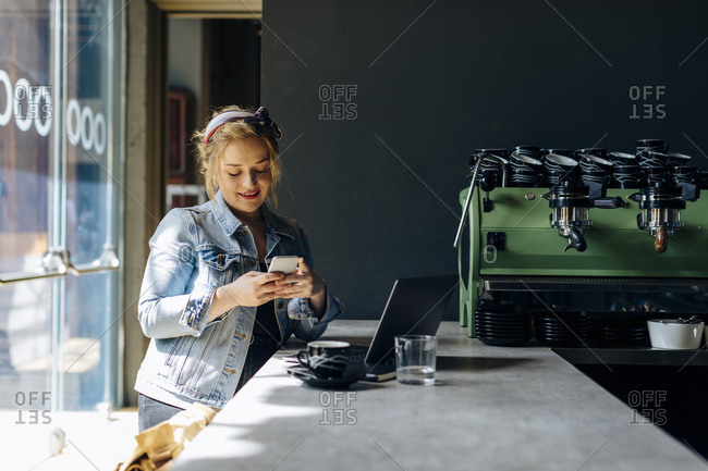 Young woman in coffee shop- using smartphone- taking pictures
